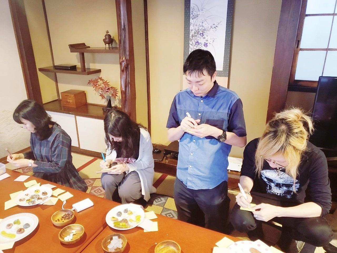 白玉で作った作品を前に、アート鑑賞している参加者たち